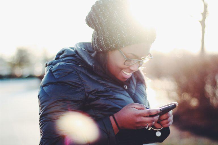 personne qui sourit en regardant son smartphone