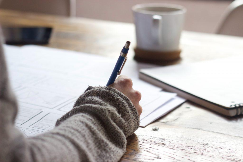 main qui écrit sur une feuille