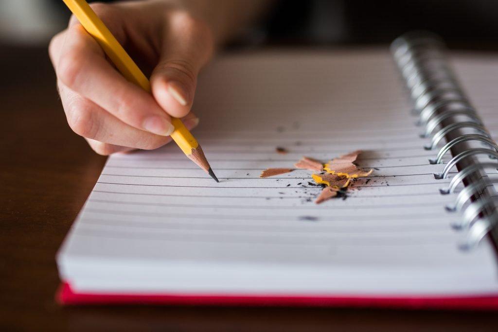 main qui écrit sur une feuille blanche